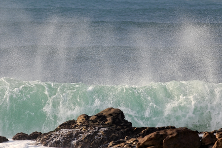 breaking in: Big green spraying wave breaking in a rocky beach from the north of Portugal