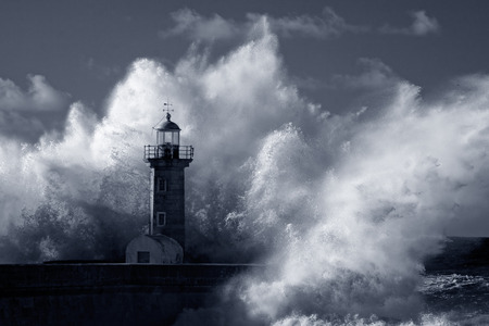 lighthouses: Big ocean stormy waves over old lighthouse of Douro mouth granite pier. Used infrared filter. Low edition photo. Toned blue.