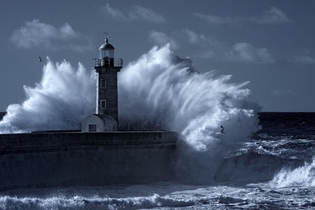 Stormy waves over old lighthouse and pier of the Douro river  mouth entry. Used infrared filter. Toned blue.