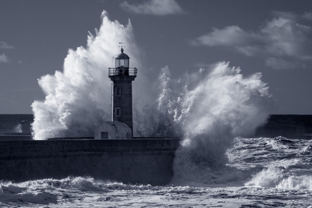 Big stormy waves over old lighthouse and pier of Douro river mouth. Used infrared filter. Toned blue