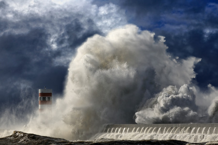 enhanced: Huge dramatic sea wave over pier and lighthouse. Enhanced sky.