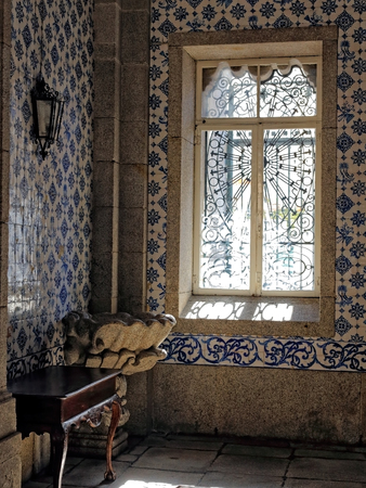 baptismal: Corner of an old European Catholic church (Porto, Portugal) with a baptismal font in granite and beautiful painted tiles on the wall, illuminated by filtrade light from a glass window. High ISO photo.