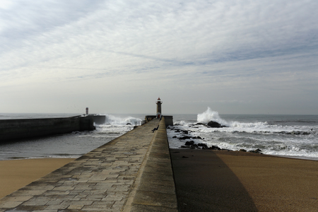 sea waves: Wide view of Douro river mouth south piers, the old and the new one, in a beautiful but stormy day during low tide