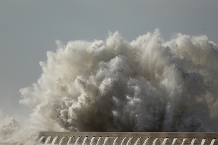 detailed image: Huge sea wave crashing against a pier from northern Portugal. Detailed image. Stock Photo