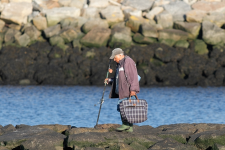 returning: Vila do Conde, Portugal - July 11, 2014: Old sport fisherman returning from a fishing session, Ave river mouth, north of Portugal.