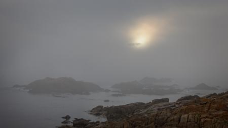 enhanced: Foggy rocky coast at sunset. Enhanced sky. Stock Photo