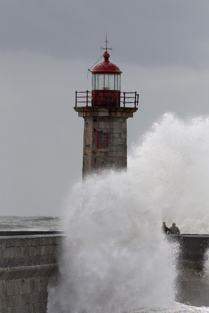 daring: Huge stormy sea waves over the old pier and lighthouse at the mouth of the Douro river seeing daring indistinct people