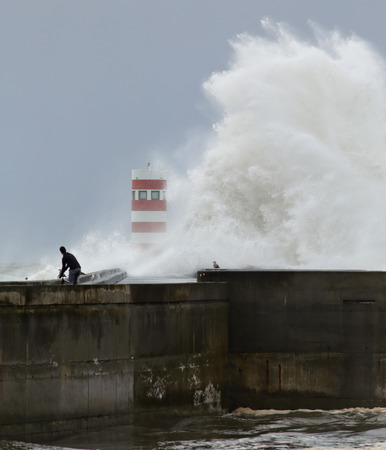 daring: Huge stormy sea wave over new pier and lighthouse at the mouth of the Douro river seeing a daring indistinct cyclist