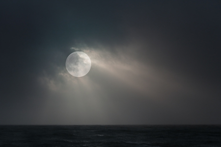 overcast: Full moon over sea in an overcast night with moonbeams