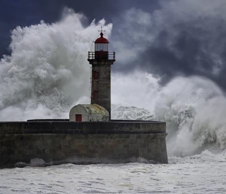 enhanced: Big stormy waves over old lighthouse. River Douro mouth, Porto, Portugal. Enhanced sky.