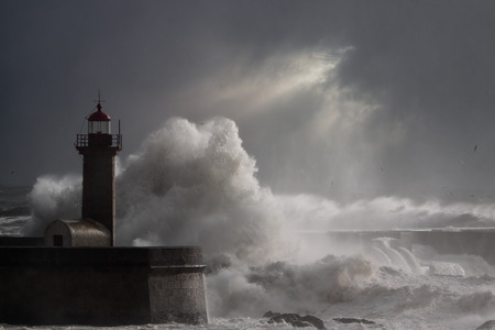 enhanced: Dramatic seascape with big stormy waves over lighthouse in a cloudy winter noon with sunbeams. Enhanced sky.