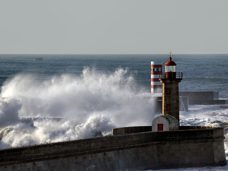 beacons: Big splashing waves with spray over piers and beacons of Douro river mouth in a sunny morning, Porto, north of Portugal Stock Photo