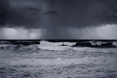 menacing: Rainy seascape with menacing clouds and interesting light. Converted black and white. Toned blue.