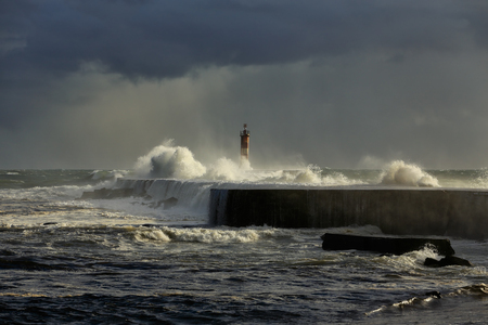 conde: Stormy sea waves over pier and lighthouse with beautiful light before rain. Ave river mouth, Vila do Conde, north of Portugal.