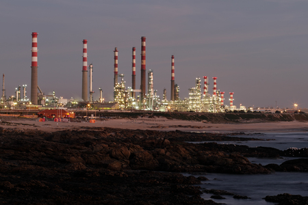 powerplant: Part of a big oil refinery and powerplant near the sea at dusk