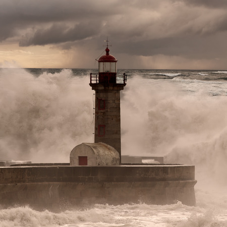 pier: Old lighthouse and pier under heavy storm. Enhanced sky. Stock Photo