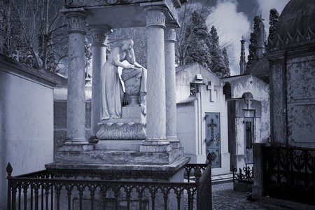 gratings: Woman statue in an old european cemetery alley. Infrared.