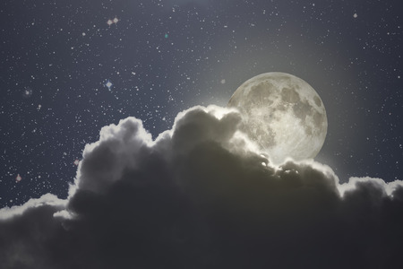 rises: Full moon rises over a cloud on a starry night