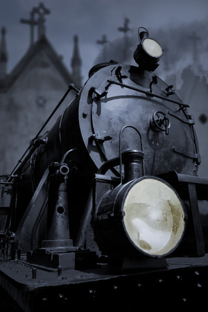 life and death: Old dark steam train in a cemetery station. Conceptual image about fear, life, death, old flaccid Europe and Caronte. Stock Photo