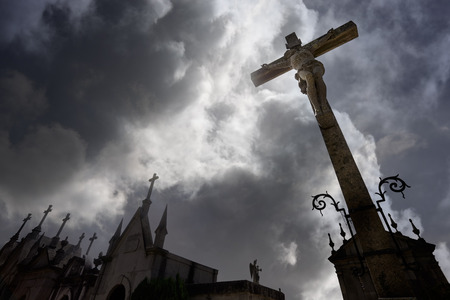 Old dark european cemetery against a dramatic cloudy sky with a crucified Christ statue on the foreground and several tombs on the form of chapels. Soft backlight. Stock Photo