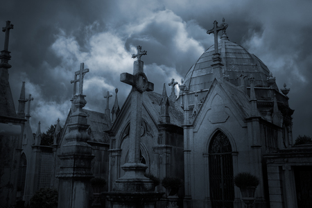 hallowmas: Old dark european cemetery against a dramatic cloudy sky with several tombs on the form of chapels and crosses.