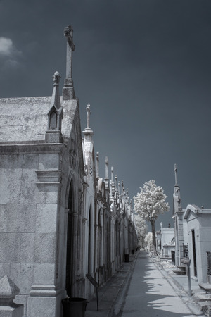 Narrow street from an old european cemetery with many tombs in the form of chapel with crosses. Used infrared filter. Toned blue.