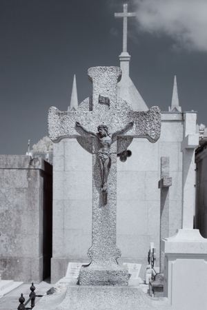 Old european cemetery bronze Christ on a granite cross. Used infrared filter.