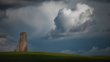 Imaginary landscape with a vast green plain, old southern european military tower and  sky with stormy clouds.