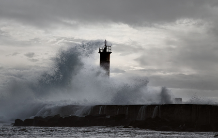 enhanced: Stormy sea wave against river Ave mouth pier and beacon with big splash. Slightly enhanced sky.