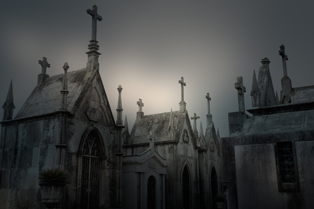 hallowmas: Old dramatic cemetery in an overcast evening Stock Photo