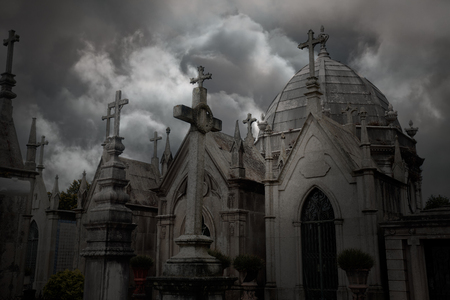 Old dark european cemetery against a dramatic cloudy sky with several tombs on the form of chapels and crosses.