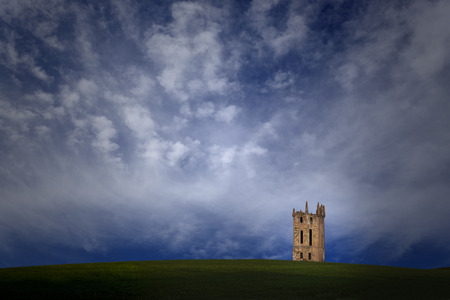 southern european: Imaginary landscape with a vast green plain, old southern european medieval tower and blue sky with some clouds. The tower is a creation of mine based on the iberic old architecture.