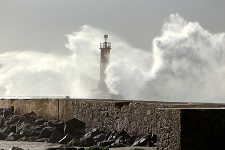 conde: Sunny stormy sea waves over pier and beacon with beautiful light. Ave river mouth, north of Portugal.