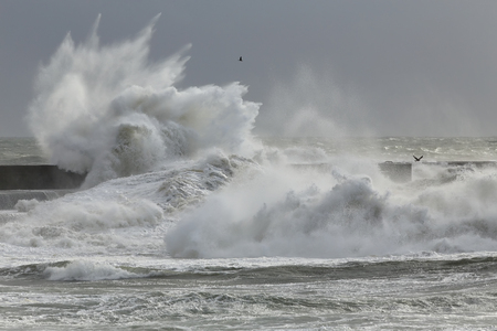 Big splash from storm waves breaking over rocks and pier Stock Photo