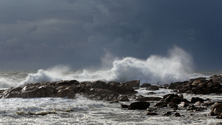 Late summer big white stormy sea waves breaking against rocks from a northern portuguese beach with an overcast blue sky before rain