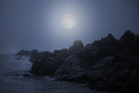 Rocky sea coast in a foggy full moon night Archivio Fotografico