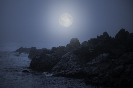 Rocky sea coast in a foggy full moon night Stock Photo