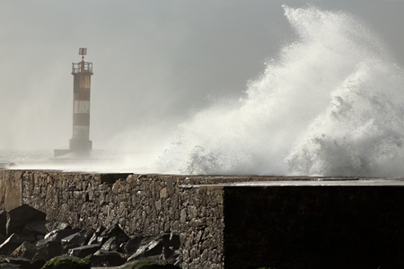 ave: Sunny stormy sea waves over pier and beacon. Ave river mouth, north of Portugal.