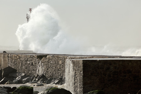 ave: Sunny stormy sea waves over pier and beacon with beautiful light. Ave river mouth, north of Portugal.