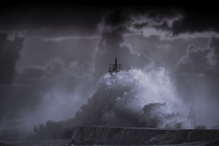 enhanced: Big storm wave against lighthouse of Ave river mouth at sunset, Vila do Conde, north of Portugal. Enhanced sky. Toned blue.