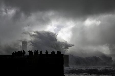 mujer mirando el horizonte: Silueta de personas en busca de una tormenta de tarde de verano del mar en el muelle de la boca del río Duero
