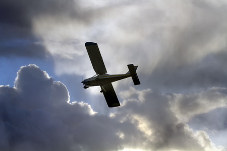 light aircraft: Soft backlit light aircraft in the clouds Stock Photo