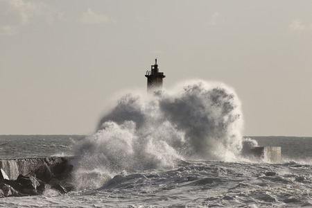 conde: Big stormy wave splash. Pier and beacon of Ave river mouth, Vila do Conde, north of Portugal. Stock Photo