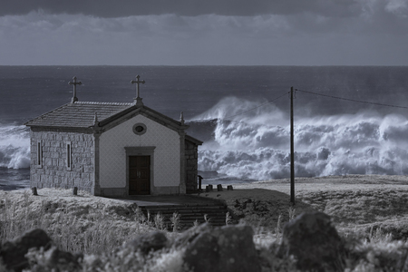 Small chapel of Saint Paio in a hill near the sea seeing stormy waves aproaching the northern portuguese coast. Used infrared filter. Toned blue. Stock Photo
