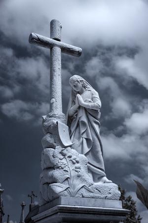 Altes europäisches Friedhofskreuz und Damenstatue. Verwendeter Infrarotfilter. Blau getönt Standard-Bild - 75466916