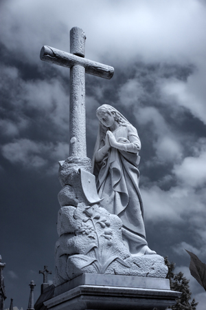 viernes santo: Old European cemetery cross and lady statue. Used infrared filter. Toned blue. Foto de archivo