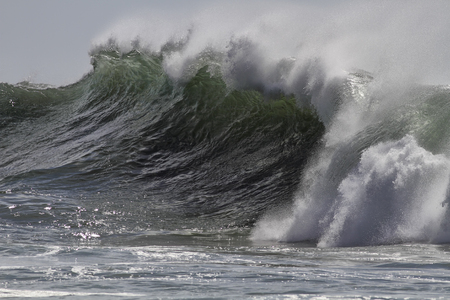 shorebreak: Big ocean breaking windy green wave with spray in a sunny afternoon. Soft backlit. Stock Photo