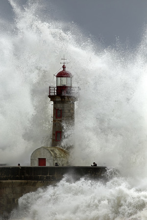 Porto, Portugal - February 7, 2016: People risking life during a sea storm in the old lighthouse (farolim de Felgueiras) at the mouth of the river Douro. Stockfoto