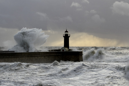 breaking: Stormy waves over pier and lighthouse at sunset Stock Photo