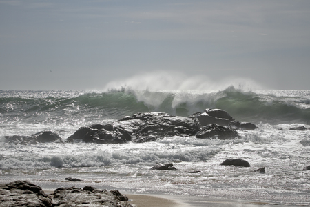 breaking: Breaking wave in a sunny day. Northern portuguese rocky coast.